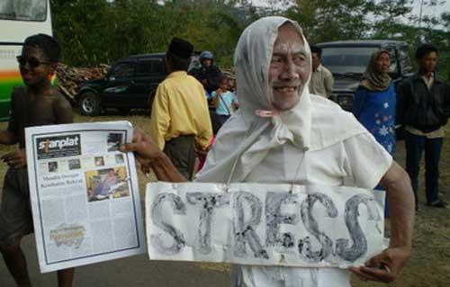 Seorang demonstran memainkan peran caleg yang sakit jiwa dalam sebuah unjuk rasa. (photo courtesy of Radar Jatim)