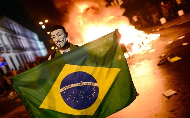 Seorang pengunjuk rasa membentangkan bendera Brazil dan mengenakan topeng Guy Fawkes, sebagai bentuk protes terhadap kebijakan pemerintah yang tidak pro-rakyat menjelang pelaksanaan Piala Dunia. (photo courtesy  telegraph.co.uk)
