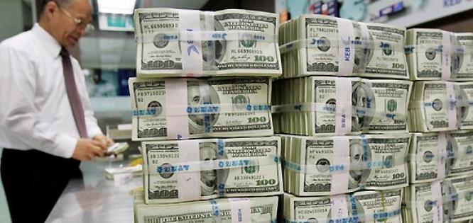 Tumpukan mata uang dolar Amerika Serikat. Cadangan devisa umumnya terdiri dari mata uang asing atau logam mulia, namun BI melakukan penjajakan atas kemungkinan bahan pangan seperti ubi jalar bisa masuk ke dalam kriteria tersebut. (photo courtesy rimanews.com)